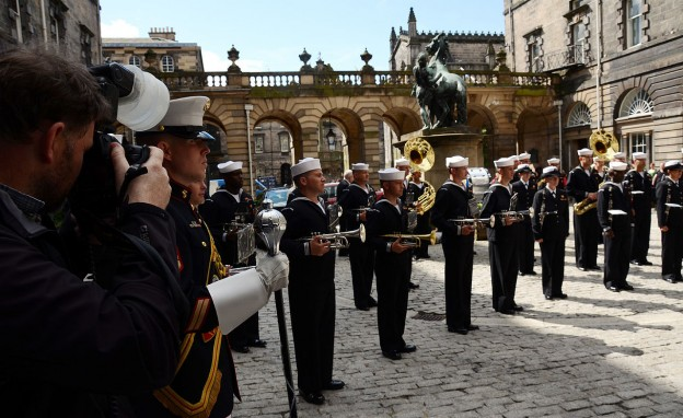 A Scottish news photographer, left, takes a photograph of the U.S. Naval Forces Europe Band at the conclusion of a concert for David Wilson, the Lord Lieutenant and Lord Provost of the city of Edinburgh, Scotland, outside the city chambers building July 30, 2012. (US DOD/MC2 Patrick Grieco via Wikimedia Creative Commons)