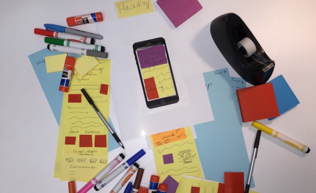 Paper and a cut-out of the iPhone 6 Plus combine to create an experience of paper prototyping for students to design long-form media for mobile devices. Illustration by Robert Gutsche, Jr.