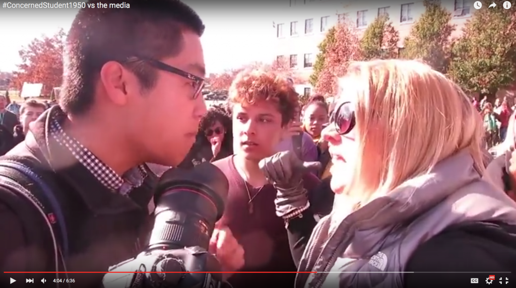 University of Missouri student photographer Tim Tai argues with protester. Taken from video by Mark Schierbecker.