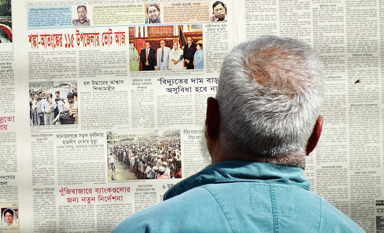 A Bangladeshi man reads a newspaper pasted to a wall in Dhaka. Photo by Adam Jones on Flickr and used here with Creative Commons license.