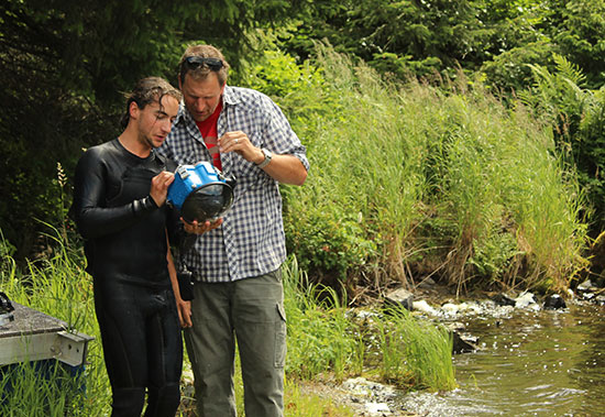 Journalism Instructor Mark Blaine assists student Will Saunders with an underwater camera housing.