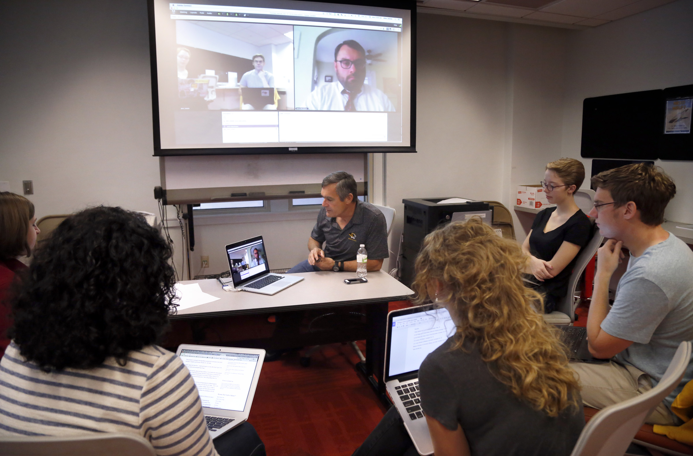 "Students in a recent class participate in a ""Star Chamber"" rating discussion with PolitiFact Executive Director Aaron Sharockman (on screen at right) and Professor Mike Jenner (center). Stephanie Mueller/Columbia Missourian"