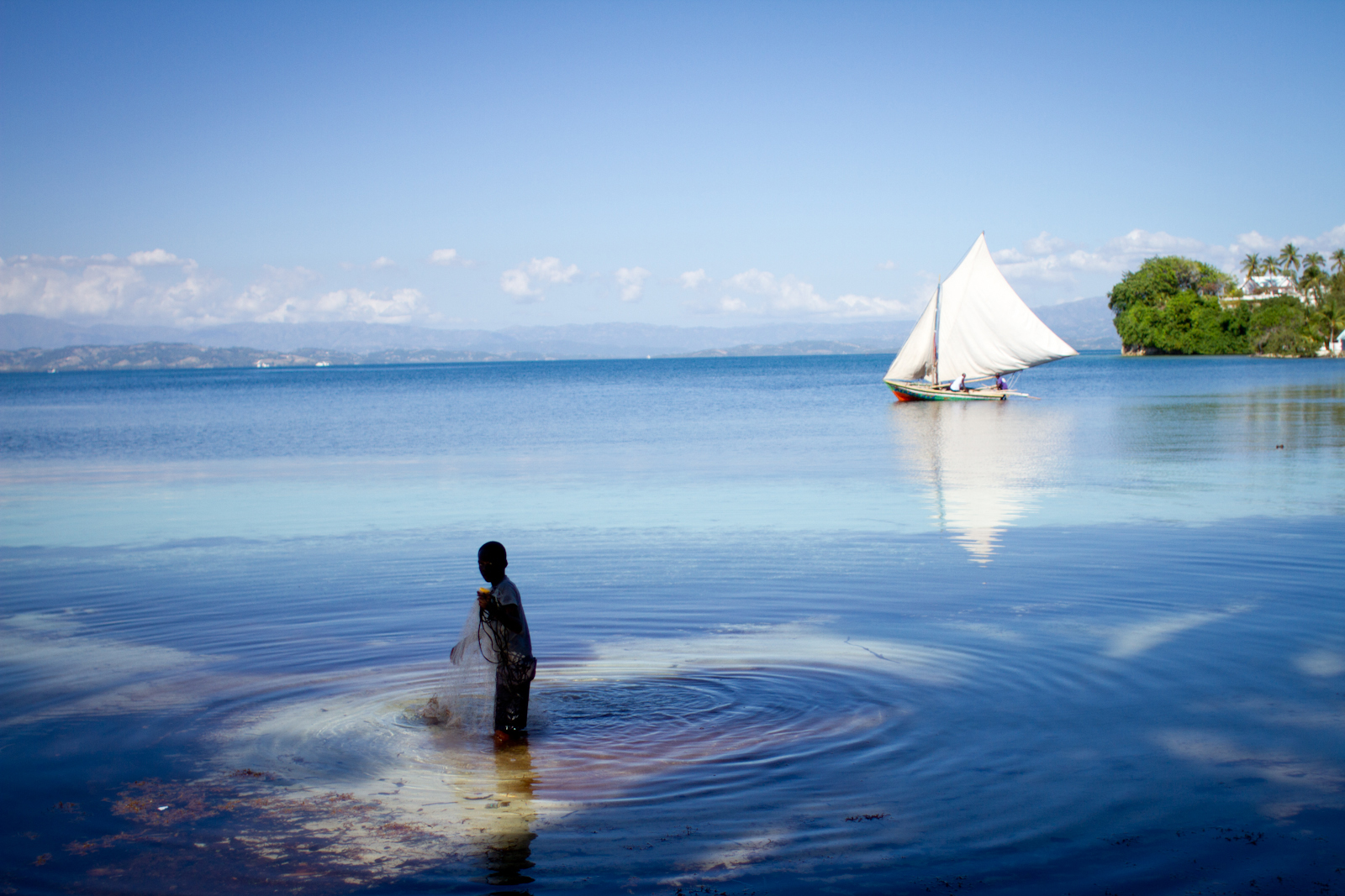 In this December 2014 photo, a boy cleans a fishing net in the waters off the Haitian island of Ile-a-Vache. haiti's southern peninsula, which was the hardest hit by Hurricane Matthew this month, is in the distance. (Photo by Jacob Kushner and used here with permission)