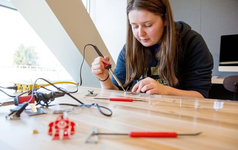Jillian Clemente solders the wires of a Makey Robot badge, used to teach soldering skills.