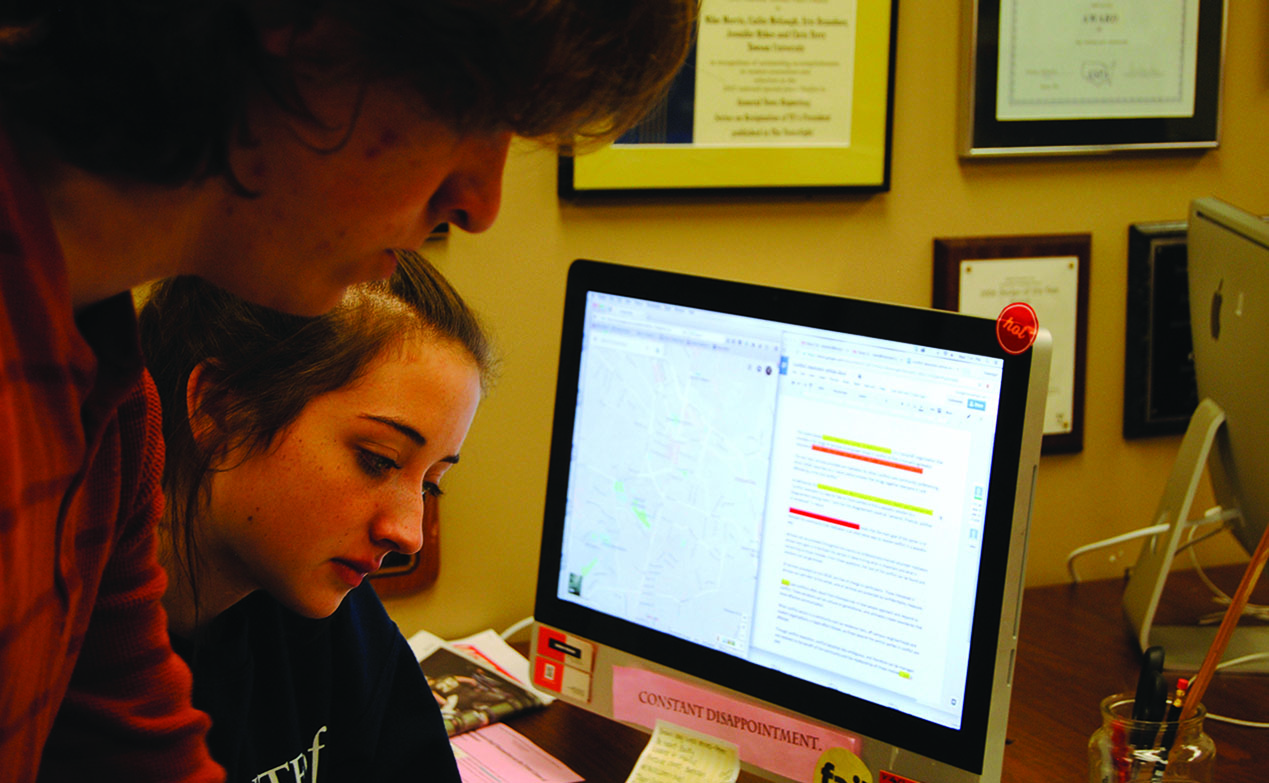 Two students compare an editing assignment with a Google map during a fact-checking exercise.