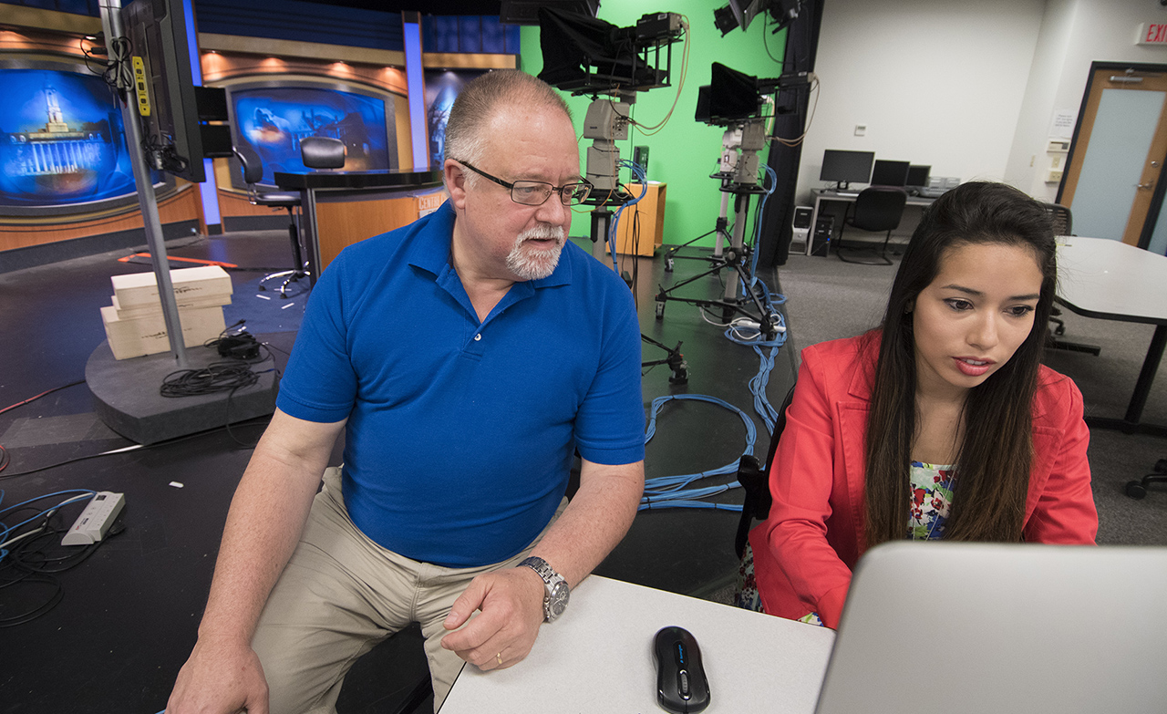 Senior lecturer Curt Chandler works with Lesly Salazar on a Verse presentation in the digital newsroom on the edge of the Centre County Report set. They are experimenting with Verse to create a new form of interactive newscast — a digicast — that allows viewers to quickly move between a tightly edited news summary and fully produced video stories. (Photo by Cameron Hart / Bellisario College of Communications | Penn State University)