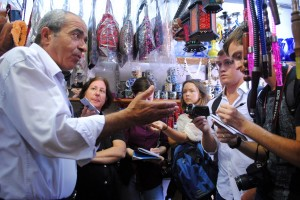 A Palestinian merchant in Hebron, left, explains the impact of the Israeli-Palestinian conflict on the local economy.