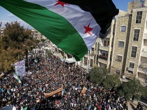 The Syria independence flag flies over a large pathering of protesters in Idlib. Photo by Freedom House on Flickr and used here with Creative Commons license.