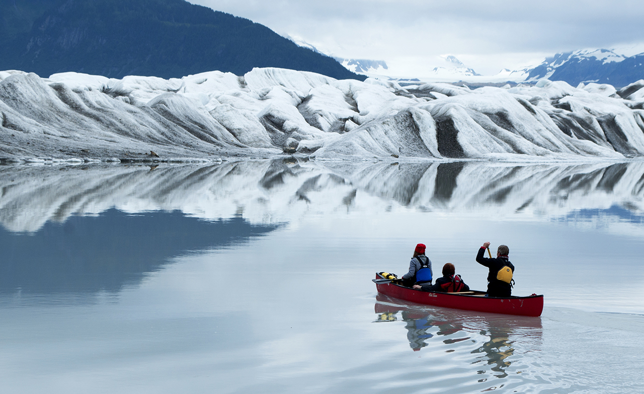 A student and faculty with the University of Oregon School of Journalism and Communication's Science and Memory program canoe into the shadow of a glacier in pursuit of a story.